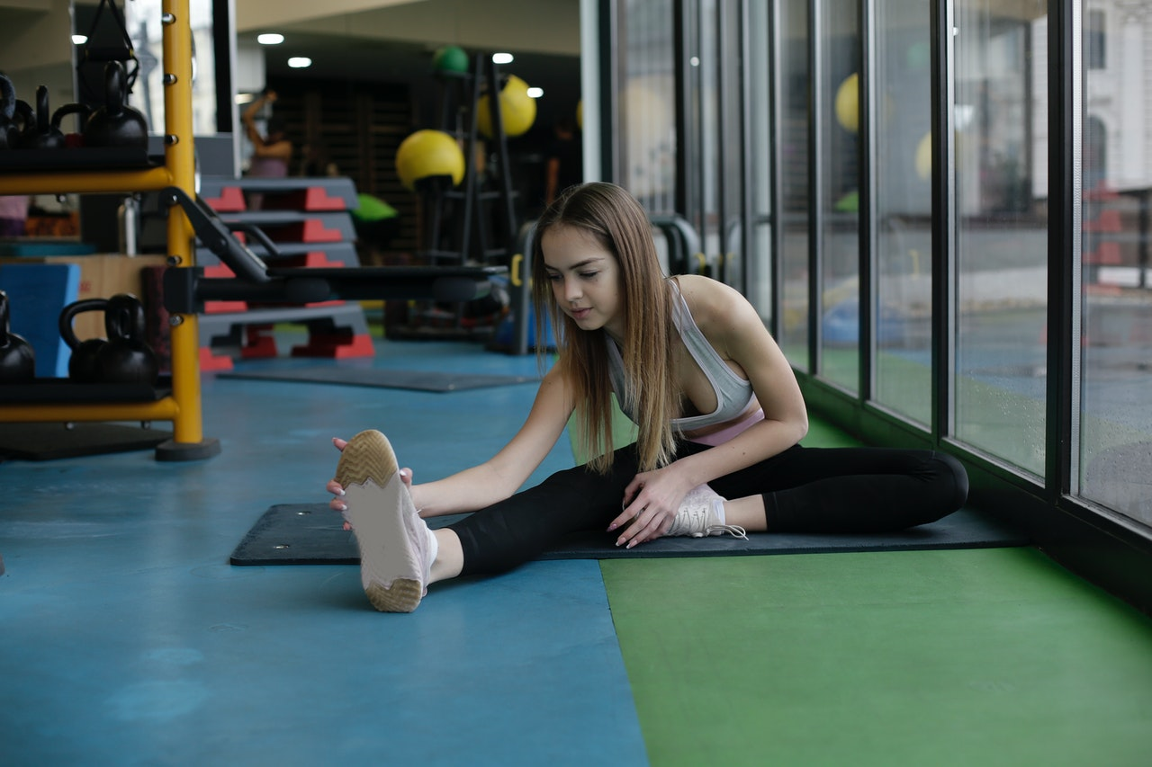flexible-young-sportswoman-doing-stretching-exercise-in-3931119