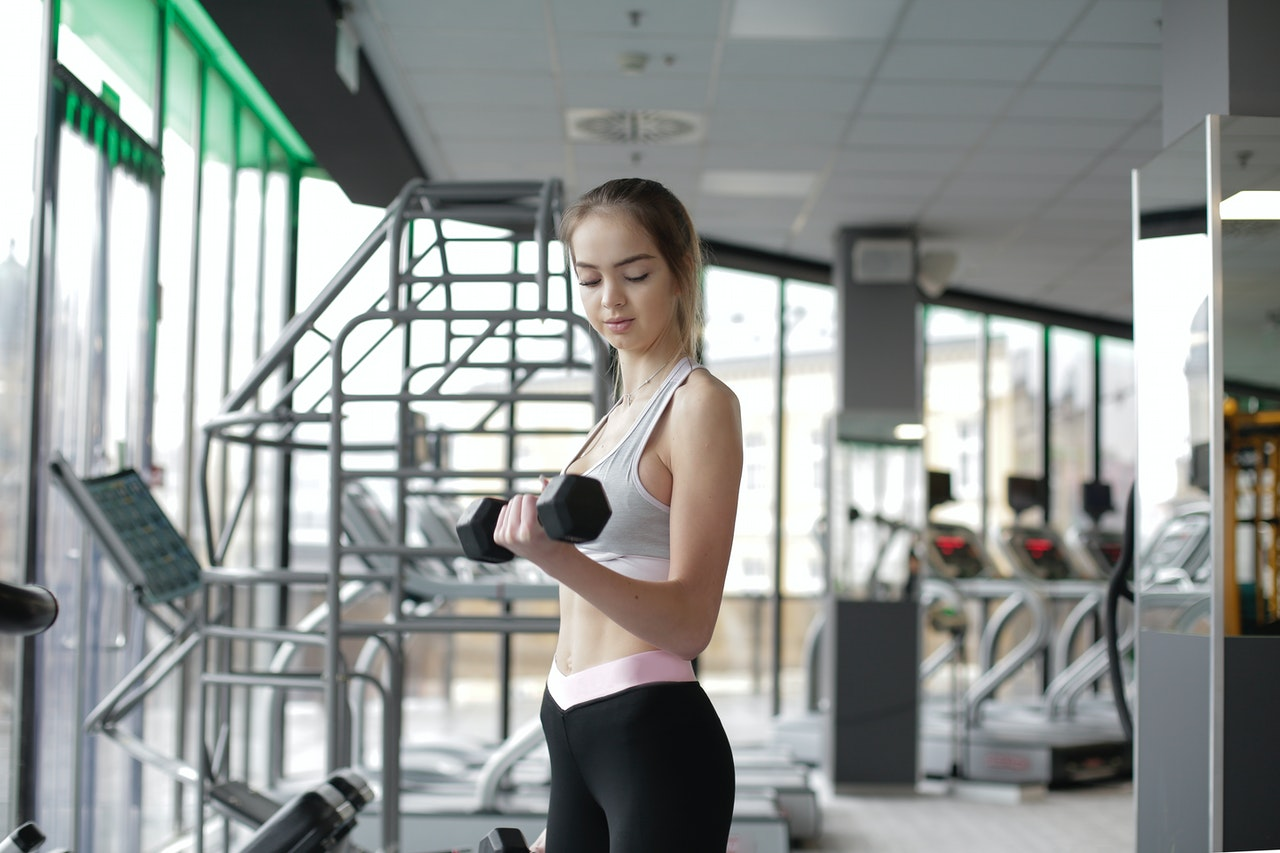 slim-young-female-athlete-exercising-with-dumbbell-in-modern-3931370