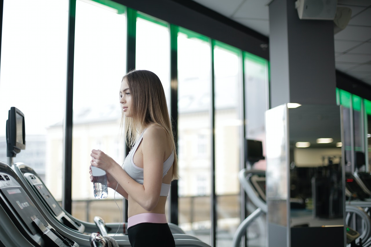 sporty-young-female-athlete-training-on-treadmill-with-3931122